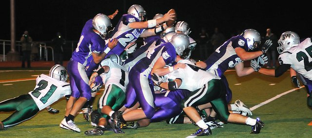 Baldwin High School senior Ryan Rogers dives over the pile of players to score a touchdown in the fourth quarter Tuesday night. Rogers also threw a pair of touchdowns to senior Josh Hoffman as Baldwin beat Blue Valley Southwest 26-7.