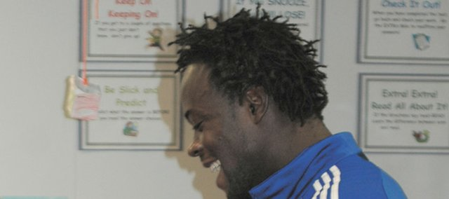 Kansas City Wizards soccer player Kei Kamara dances with Prairie Ridge Elementary School third-grader Alicia Baker. Kamara made a surprise visit Friday to the classroom. Students had written letters to Kamara earlier in the month. He also will be sending the class's homemade book projects to his home country, Sierra Leone.