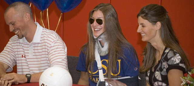 Tonganoxie High senior Molly O'Hagan laughs with volleyball co-coaches Brandon and Tiffany Parker on Tuesday, Nov. 9 after signing a letter of intent with Cal State University Bakersfield. O'Hagan had to wear sunglasses, a neck brace and a sling due to injuries she suffered in a Nov. 3 car accident.
