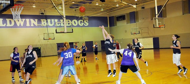 Baldwin High School sophomore Kailyn Smith, center, attempts a shot during practice Tuesday.