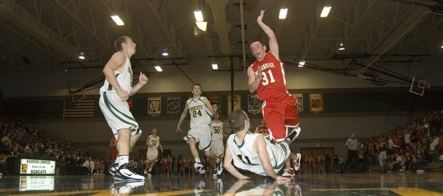 Basehor-Linwood High senior guard Evan Theno draws a charge against Tonganoxie senior guard Jeremy Carlisle in the first half of the Bobcats&#39; 62-30 victory to open the season Friday night at Basehor.