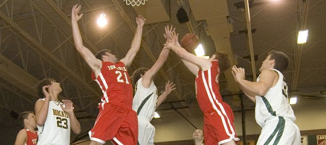 Tonganoxie High post players Brady Waldeier (21) and Dane Erickson reach for a rebound as it gets batted away at Basehor-Linwood on Friday. The Chieftains lost their season opener against the Bobcats, 62-30.