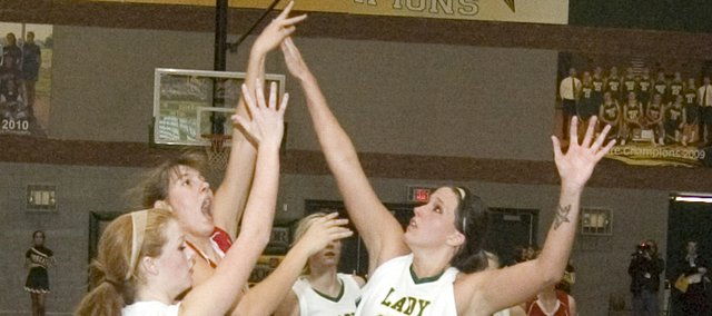 Emma Stilgenbauer puts up a shot over the arms of Bobcats Victoria Smith (34) and Megan Bergstrom (23) in the paint on Friday at Basehor-Linwood. Tonganoxie held a three-point halftime lead in its season opener before falling, 31-28, at BLHS.