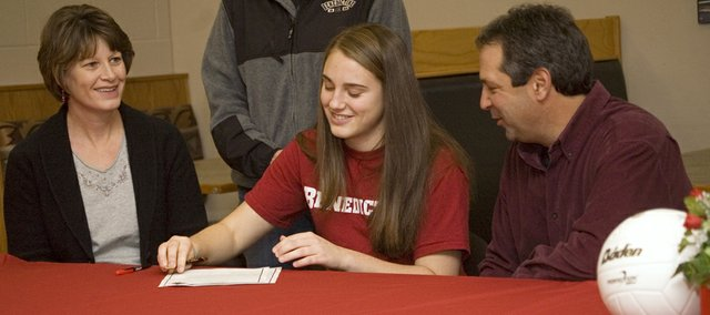 Tonganoxie High senior Danielle Miller signs to play volleyball for Benedictine College as her parents, Jennie and Steve Miller look on Tuesday, Dec. 7 at THS.