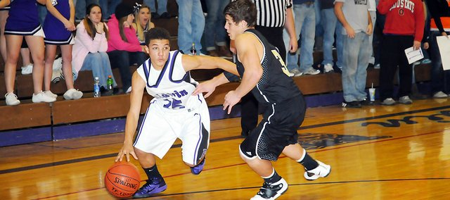 Baldwin High School freshman Cornell Brown, left, dribbles around Paola's Austin Dent during the second quarter Tuesday. Brown scored 13 points as Baldwin beat Paola 53-42 to win its home and Frontier League opener.