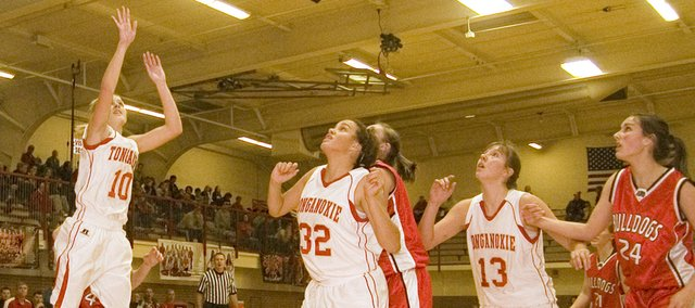 Tonganoxie High sophomore point guard Madee Walker puts up a shot after grabbing an offensive rebound against Anderson County on Dec. 17, as teammates Tavia Brown and Emma Stilgenbauer fight for position in the paint.