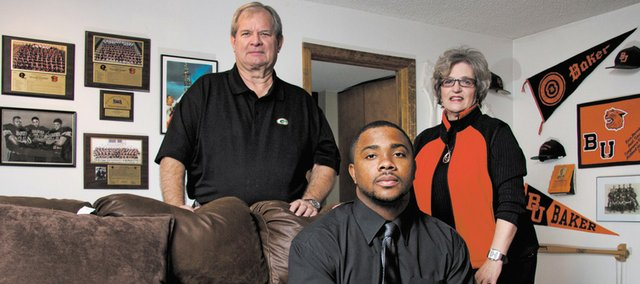 Richie Bryant, center, a fifth-year senior at Baker University, graduated over the weekend. Pictured with Bryant are Dan Harris, the former athletic director at Baker, and his wife, Peggy, the dean of education at Baker. The Harrises took Bryant into their home, giving him a place to live as he finished his degree.