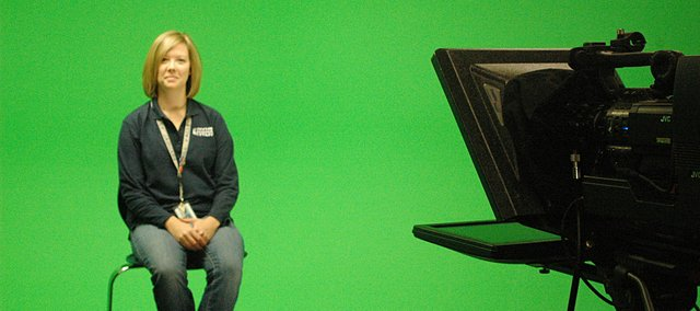Broadcast teacher Cindy Swartz demonstrates how the new Mill Valley High School broadcast studio's green screen works.