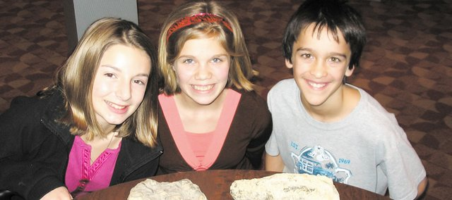 Paige Krone, Leelynn Bogan and Parker Capehart (from left) were part of the sixth-grade classes at Clark Middle School that found fossils like those shown above in an area quarry.
