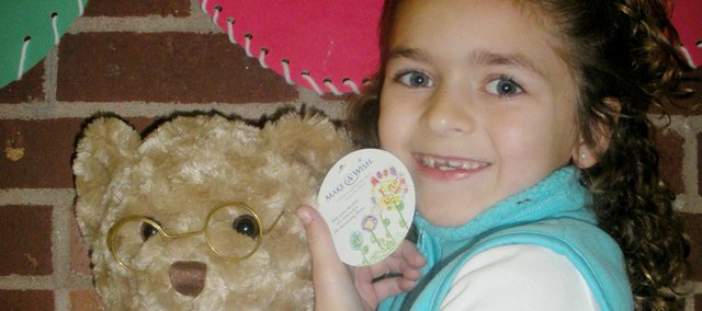 Jillian Sharp, Bluejacket-Flint Elementary School first-grader, shows off her Helzberg Diamond teddy bear. Jillian designed the tag featured on the bear. A portion of the proceeds from the bear go to the Make-A-Wish Foundation. In 2009, Jillian received her wish for a trip to Disney World.