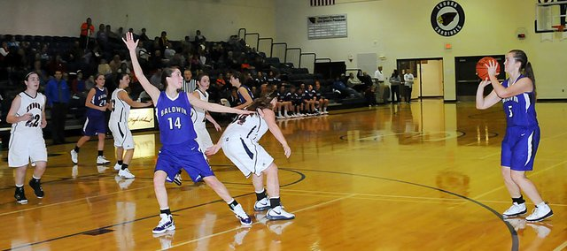 Baldwin High School senior Allison Howard, right, shoots a three-pointer during the second quarter Monday night. Howard scored 13 points as the Bulldogs won 54-31.