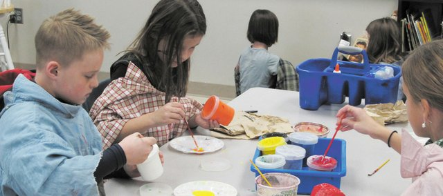 Clear Creek Elementary School fourth-grade students (from left) Cole Moore, Demi Vanmeerhaeghe and Jessica Leininger paint pop art sculptures. The school's page on Artsonia Online Children's Museum is number one in Kansas.