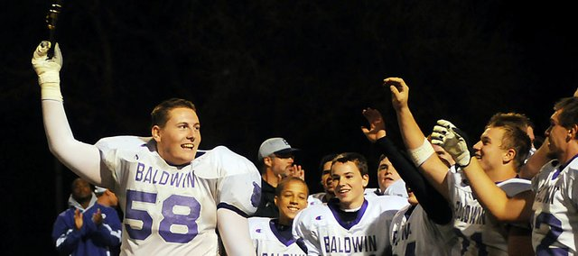 Baldwin High School senior Jesse Austin (No. 58) hoists the Bulldogs state playoff plaque during the fall. Austin was recently chosen to play in the Kansas Shrine Bowl in July.