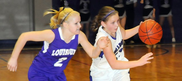 Baldwin High School sophomore Kailyn Smith, right, dribbles around Louisburg's Madison Wertz during the third quarter Friday night. Smith scored 11 points in the Bulldogs' 56-44 victory.