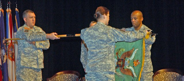In a ceremony marking the 40th Military Police Battalion's deployment to Iraq, 15th Military Police Brigade Commandant Col. Eric Belcher holds the unit's colors as Lt. Col. Erica Nelson, unit commander, and Command Sgt. Maj. Donald Wallace prepare to wrap it for shipment. When the unit will be one of the last to leave Iraq when it completes its yearlong mission.