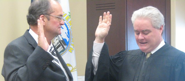 Bob Holland (left) takes the oath of office as he is sworn in as a Leavenworth County Commissioner by 1st District Judge Dan Wiley at the Leavenworth County Courthouse Monday.