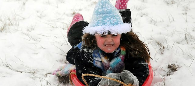 Abby Patterson enjoys her snow day from school as she sleds down the hill near Baldwin Elementary School Intermediate Center. Although Signal Oak hill remains the top spot for sledding around Baldwin City, the hill near BESIC is used by may families and younger children.