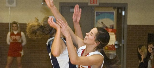 Tonganoxie High sophomore Jenny Whitledge is hit in the backcourt by a Mill Valley defender while making a pass out of a trap on Friday during the Chieftains' 52-28 home loss to the Jaguars.