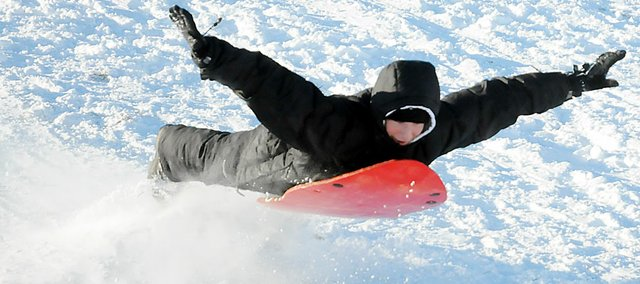 Baldwin High School junior Alex Twombly soars through the air while sledding Tuesday. Twombly and  other youngsters were released from school Monday and Tuesday and many of them spent time outside sledding.
