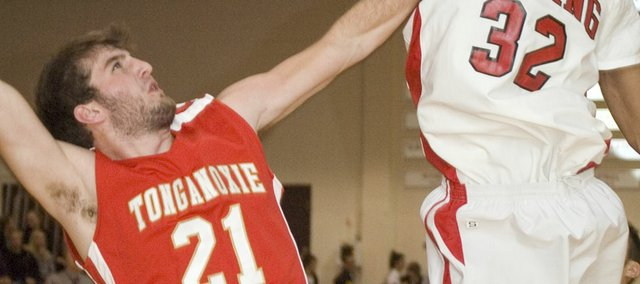 Tonganoxie High junior forward Brady Waldeier tries to fend off Lansing's Chris Jones under the basket in the third quarter of the Chieftains' 60-30 road loss on Friday.