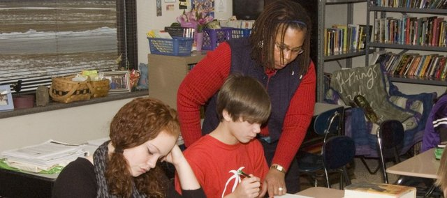 "Tonganoxie Middle School teacher Debbie Holloway assists Milton Ulreich with an English assignment Tuesday as Haleigh Peel also works on the assignment. Holloway had students compare and contrast Martin Luther King Jr.'s ""I Have a Dream"" speech with President Abraham Lincoln's Gettysburg Address."