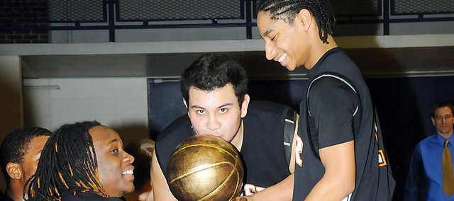 Bonner Springs High School senior Juan Pichardo kisses the Braves' trophy after they won the Baldwin Invitational Tournament Saturday. The Braves have won the BIT in back-to-back years.