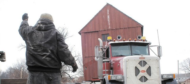 John Earnshaw guides the truck while moving the Shawnee Town barn in December. The barn is a fraction of the size of many structures he's moved over the years.