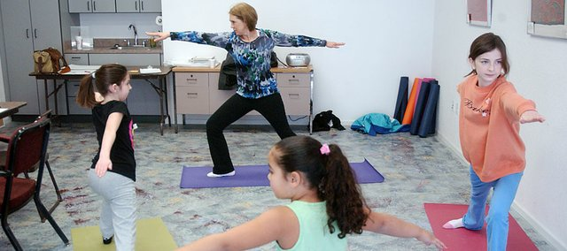 Instructor Jane Taul demonstrates the yoga warrior pose to Emma Bailey, right, Aleena Houston, center, and Addy Trendel during a Lumberyard Arts Center class that blends yoga and art.