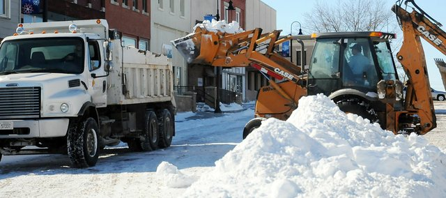Baldwin City crews work to remove the snow from the downtown area Wednesday morning. The snow stopped falling Tuesday night and crews began removing the piles of snow Wednesday.