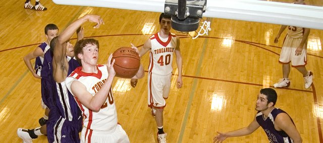 Tonganoxie High junior center Dane Erickson keeps the ball away from a Piper defender in the second quarter of Tonganoxie High's 70-66 home win on Friday. Erickson shot 13-for-13 from the field and finished with 30 points.