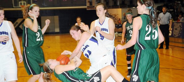 Baldwin High School senior Ramie Burkhart and De Soto senior Jesse Spencer get tangled up with the ball as they fall to the ground Monday night. The Frontier League matchup was physical, but Baldwin prevailed with a 43-36 victory.