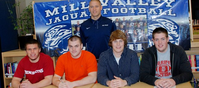 Mill Valley football coach Joel Applebee, standing, celebrated his first signing class as the Jaguars' head coach on Monday in the MVHSmedia center. Players who signed are, from left, Jeremy Spalding (Benedictine College), Leo Beck (Fort Scott Community College), Kyle Brunson (Fort Scott) and Jordan Bath (Coffeyville).