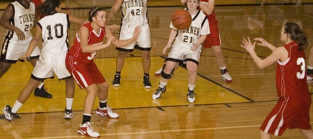Tonganoxie High forward Tavia Brown kicks the ball out to an open Haley Smith in the second quarter of the Chieftains' easy, 49-19 road win Thursday at Turner.