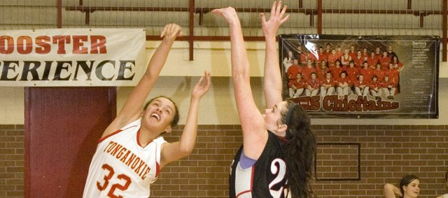 Tavia Brown draws a foul on Lansing High's Katie Delich in the third quarter of Tonganoxie's 59-51 victory over LHS on Tuesday.