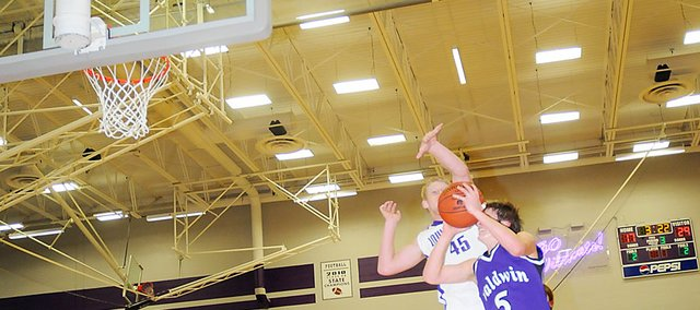 Baldwin High School senior Kyle Pattrick draws a foul from Louisburg's Garrett Griffin at he attempts a layup during the third quarter Tuesday. Pattrick made both free throws after Griffin committed his fourth foul. Baldwin won the game 37-35.