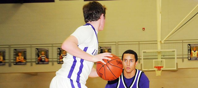 Baldwin High School junior Asher Hannon, right, stares down a Louisburg player while focusing on playing full-court defense Tuesday night at Louisburg. BHS won the game 37-35.