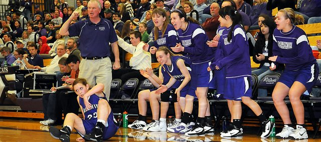 Baldwin High School coach Bob Martin and players on the bench react to a three-pointer made by sophomore Kailyn Smith, seated on the court, late in the third quarter Tuesday. Smith was fouled on the shot. She converted the four-point play to tie the game. It propelled Baldwin to victory as it won 46-36.