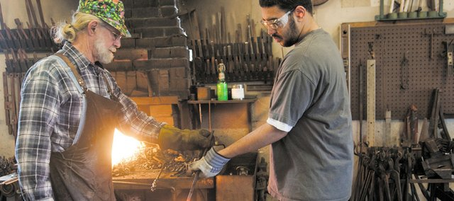 Walt Hull, left, teaches Van Go Mobile Arts artist Miquel Brown, 18, how to forge a piece of iron at Walt Hull Ironworks Thursday, Feb. 17, 2011.