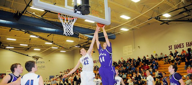 Baldwin High School senior Justin Vander Tuig attempts a layup while heavily guarded Monday night. Vander Tuig made the shot and scored 16 points to lead the Bulldogs in their 54-43 loss Monday night at St. James.