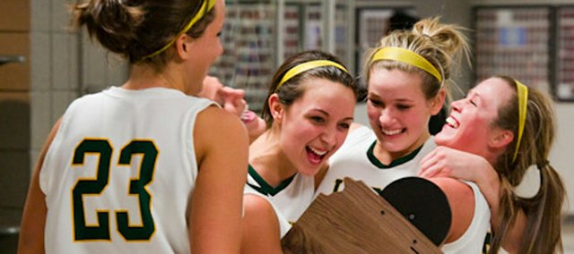 Basehor-Linwood girls basketball seniors, from left, Megan Bergstrom, Courtney Poe, Macyn Sanders and Amanda O'Bryan celebrate with the Class 4A substate championship trophy Saturday night at Piper High School. The Bobcats defeated Sumner Academy in the finals, 41-37, and secured their second straight trip to the state tournament.