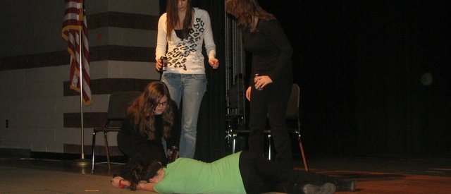 "From left, Jessica Morris, Cammie Mitchener and Sky Morrell arise from their chairs after Emily Lynch collapses during a rehearsal of ""Under the Influence,"" the Basehor-Linwood High School spring play. Before and after the performances this week, representatives will be available from drug and alcohol treatment organizations in the area."