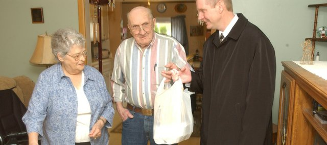 Tonganoxie Mayor Jason Ward hands a noonday meal of ham and beans last Thursday to Becky and Glenn Sharp of Tonganoxie. The couple are among about 40 Tonganoxie residents served by the Leavenworth Council on Aging Meals on Wheels program. Ward helped deliver meals as part of a monthlong Mayors and Wheels campaign.