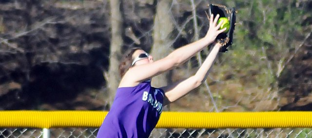Baldwin High School junior Kaysha Green stretches out her arms as she makes a catch over her head in left field Tuesday. BHS lost both games at Ottawa.