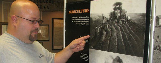Dennis Mertz, co-owner of JED Installation and Basehor City Council member, discusses the old agricultural equipment captured in some of F.M. Steele's early 20th-Century photography. An exhibit of Steele's photos is on display this month at the Basehor Historical Museum.