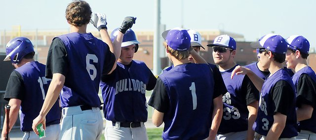 Baldwin High School senior Josh Hoffman, center, is joined at home plate by his teammates after hitting a two-run home run in the first game Tuesday.