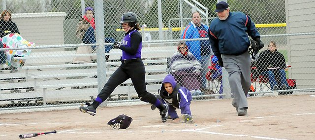 Baldwin High School freshman Hailey Cope avoids the tag from the Louisburg catcher as she crosses home plate Tuesday. Cope's run sparked a five-run rally as BHS swept Louisburg.