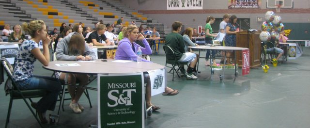 During an academic awards ceremony at Basehor-Linwood High School on April 28, seniors sit at tables with signs displaying their college choices.