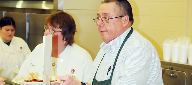 Darrell Bowersox serves a lunch Tuesday at Baker University's Harter Union cafeteria. The Baker University directory of food services will retire June 30 after 26 years on the job, during which he introduced higher standards in food service. The university will honor Bowersox with a reception from 2 to 4:30 p.m. Wednesday at Collins House.