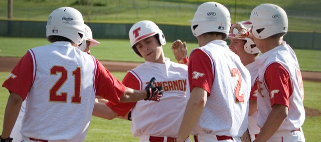 Tonganoxie High freshman Shane Levy is greeted by his teammates at home plate after hitting a grand slam Friday at Leavenworth County Fairgrounds against Bonner Springs. Levy's home run helped THS win Game 2 of a doubleheader, 8-4, after the Braves won Game 1, 3-2.