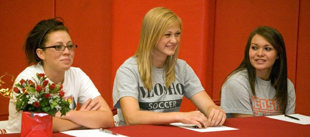 Tonganoxie High soccer seniors Carlea Richert, Ashley Kotowske and Grae Wilbanks sit side-by-side for their college signing ceremony on Friday at Tonganoxie High. Richert signed with Independence Community College and both Kotowske and Wilbanks signed with Neosho County Community College.